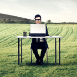 man typing at desk in middle of a field