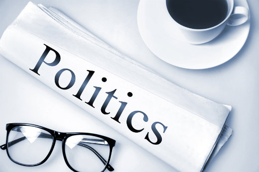 "illustration of the word ""politics"" on a rolled up newspaper"