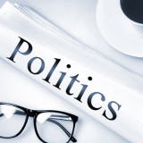 """the word """"politics"""" on a rolled up newspaper"""
