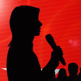 silhouette of woman speaking into a microphone