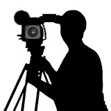 person using a video camera in silhouette