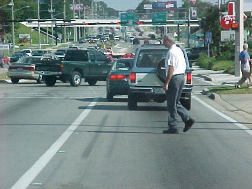 Man crossing busy arterial roadway.