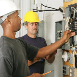 photo of electricians examining wiring