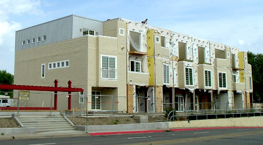 3 story high residential apartment building made up of manufactured housing units.
