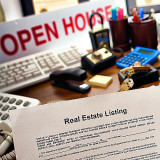 Photo of realtor's office with open house sign and view of real estate listing