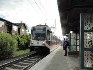 MAX light rail train arriving at Orenco Station from Hillsboro, heading to Portland and Gresham.