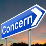 "Directional sign with the word ""Concern"" on it."