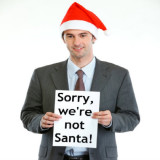 Businessman with Sorry We're Not Santa sign